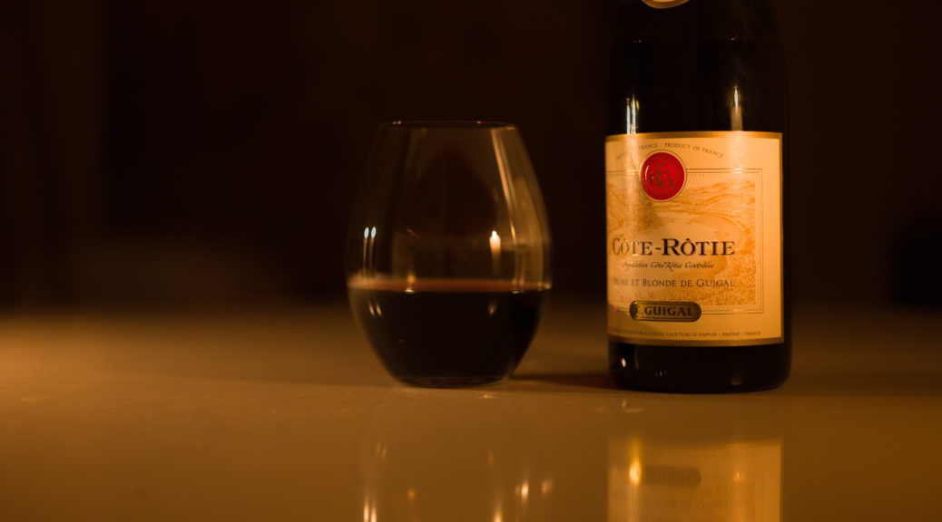 Candlelight photo of glass of wine and a bottle of E. Guigal Cote-Rotie Brune & Blonde de Guigal 2011.