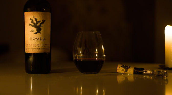 Candlelight photo of bottle of Bogle Essential Red wine, with a glass and the cork.