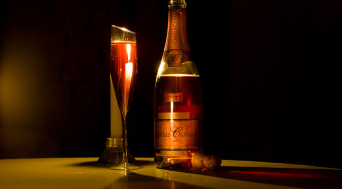 Candlelight photo of brut rose cava wine bottle and glass of wine, with a candle behind the glass.