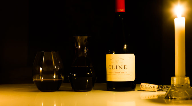Candlelight photograph of wine bottle, carafe, glass, and cork.