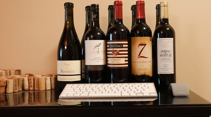A computer keyboard, mouse, and wine bottles, as if the bottles are the display.